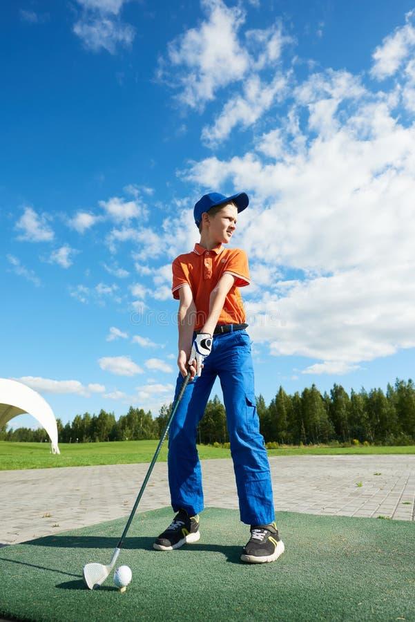 打高尔夫球的男孩在领域在夏天 免版税库存照片