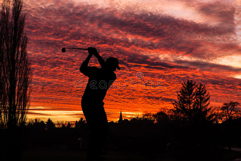 打高尔夫球的高尔夫球运动员在日落期间在竞争事件 免版税库存图片