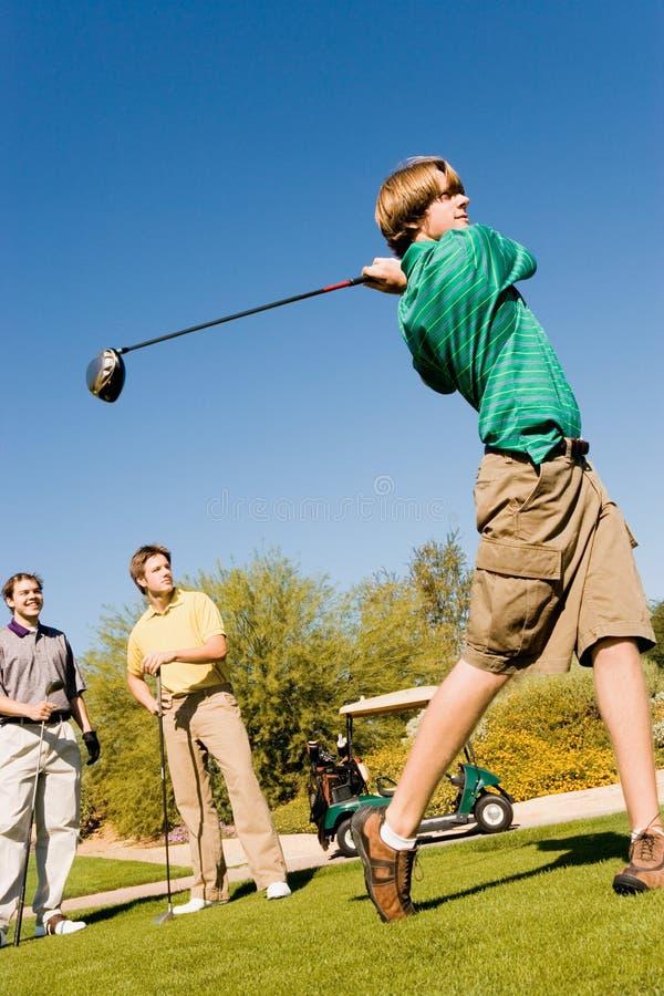 打高尔夫球的年轻朋友 免版税库存照片