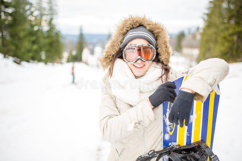 打鼾的 有拿着她的雪板的滑雪帽的年轻美丽的妇女在滑雪胜地的滑雪倾斜少妇 免版税库存照片