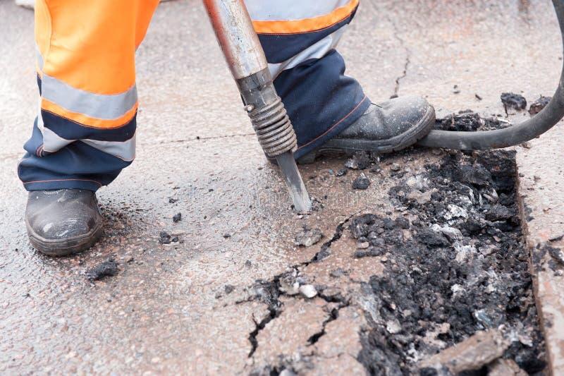 打破与手提凿岩机的路工作者街道沥青 免版税图库摄影