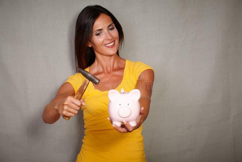 打破与锤子的微笑的年轻人moneybox 免版税库存图片