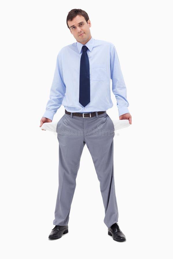 打破了显示他空的口袋的商人 免版税库存照片