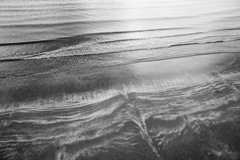 打破在海滩的波浪顶上的空中射击  库存照片