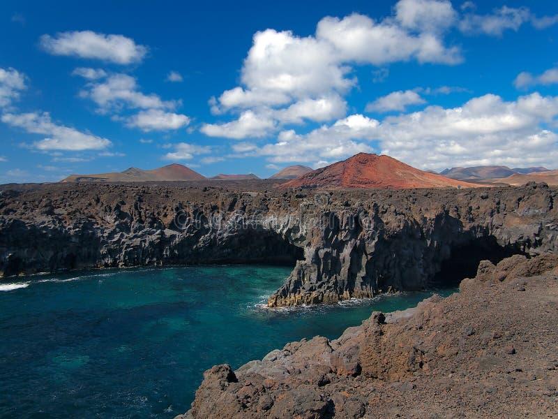 打破在被硬化的熔岩岩石海岸的海浪与洞穴和洞的 与白色云彩和山的深蓝天 免版税库存图片