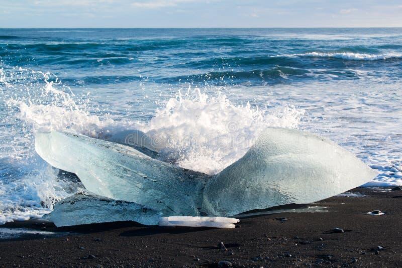打破在黑沙子的一座冰山的波浪在Jokulsarlon冰盐水湖,冰岛靠岸 库存图片