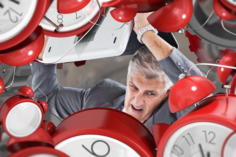 打破膝上型计算机的恼怒的商人的综合图象 免版税库存照片