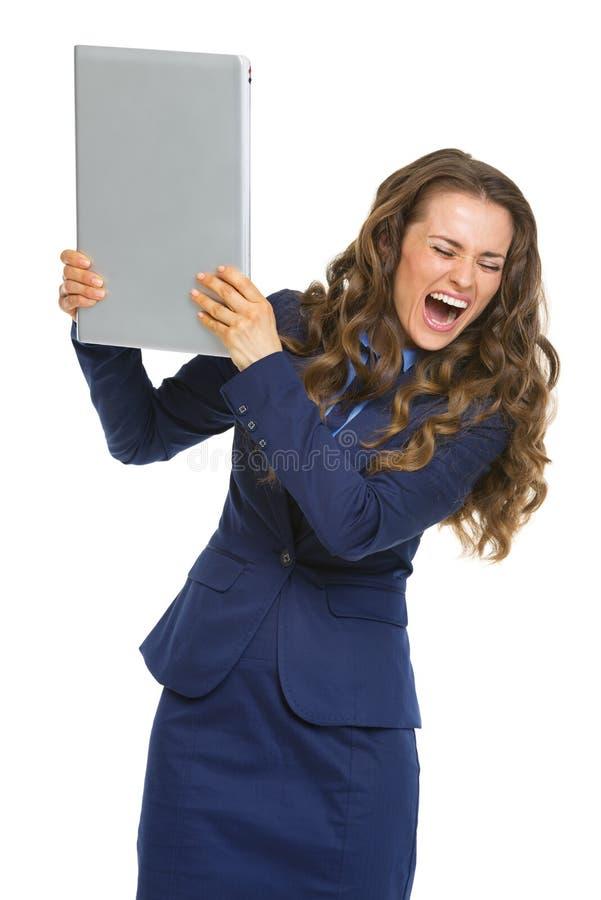 打破膝上型计算机的恼怒的女商人 库存照片