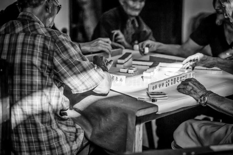 打Mahjong在影片l的老中国人民中国打牌 库存图片