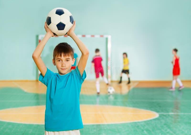 扔足球的男孩在足球比赛期间 库存图片