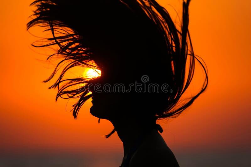 扔头发的妇女剪影在日落 图库摄影