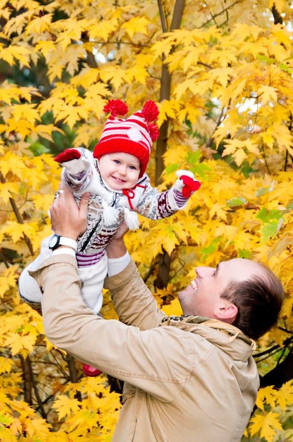 扔他的小女儿的愉快的父亲 免版税图库摄影