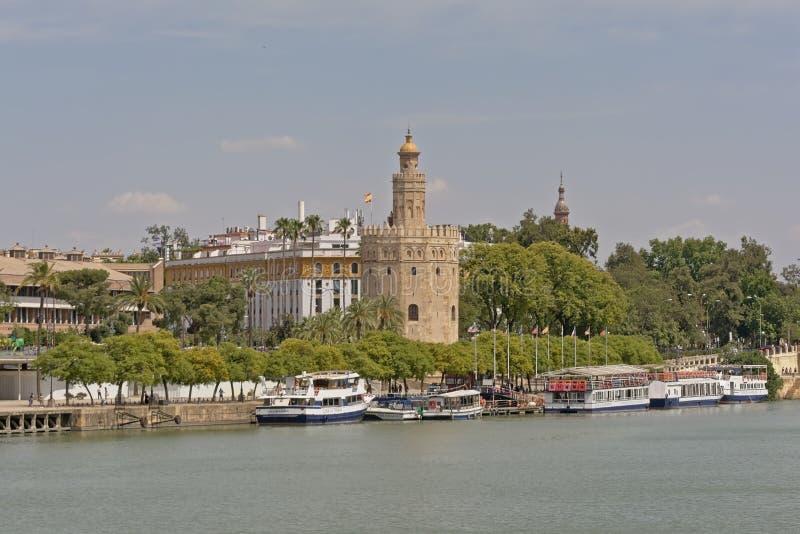托尔del Oro,沿瓜达尔基维尔河河的历史城楼有在前面的游船的在塞维利亚 库存图片