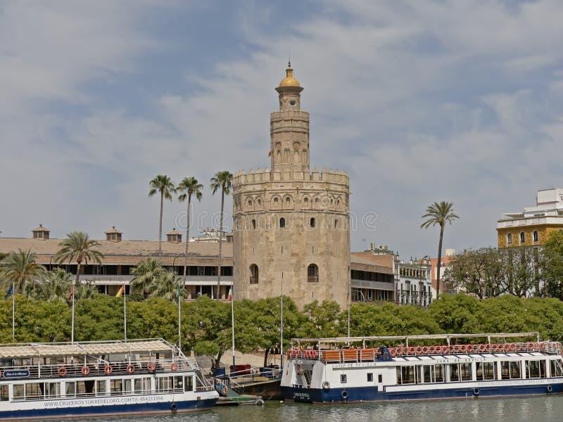 托尔del Oro,沿瓜达尔基维尔河河的历史城楼有游船的在塞维利亚 免版税库存照片