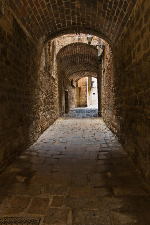 托斯卡纳沃尔泰拉狭窄通道中中世纪石砖房屋的建筑细节 库存照片