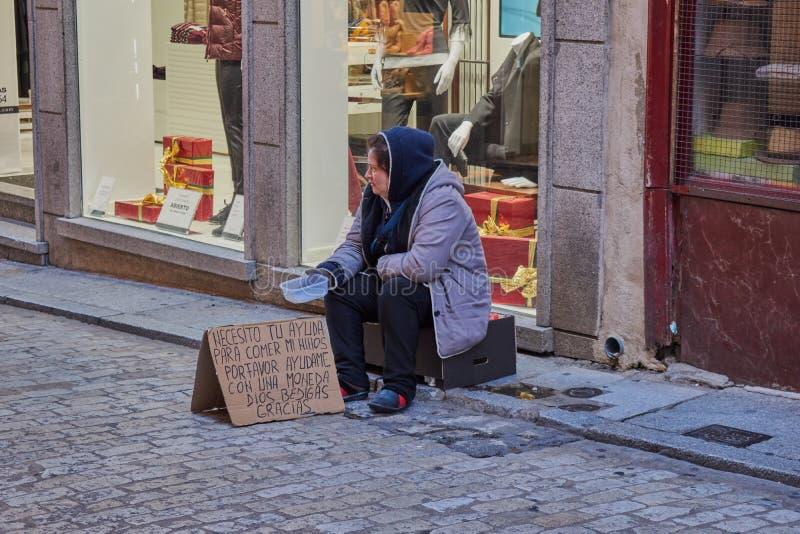 托莱多,西班牙;12月23日2日 017 :坐在纸板箱的一名哀伤的未认出的无家可归的妇女要求乞求金钱的能吃 库存图片