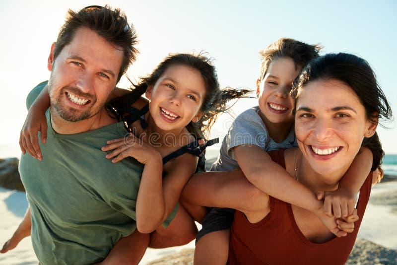 扛在肩上他们的在海滩的中间成人白父母孩子,微笑对照相机,关闭,由后照 免版税库存图片