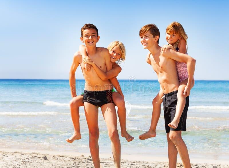 扛在肩上他们的海滩的愉快的男孩朋友 库存图片