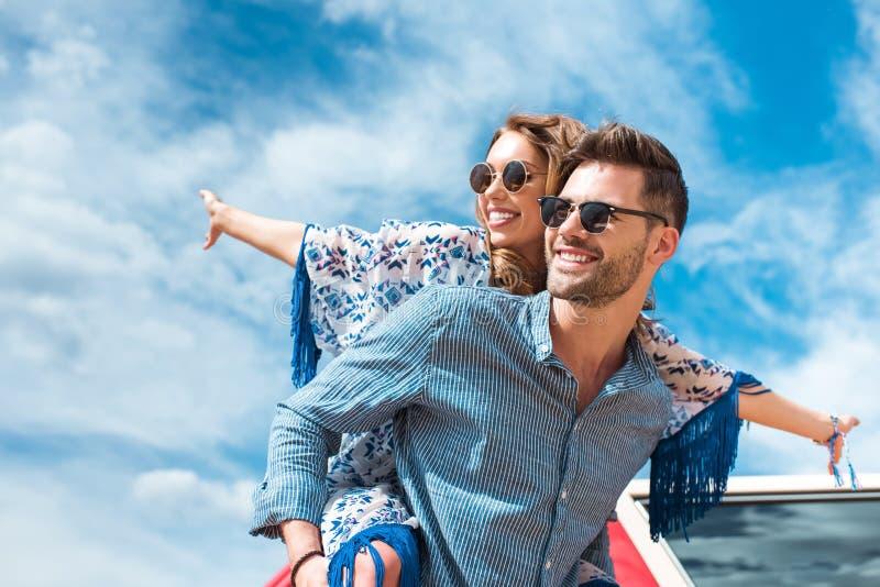 扛在肩上他微笑的女朋友的愉快的人 免版税库存图片