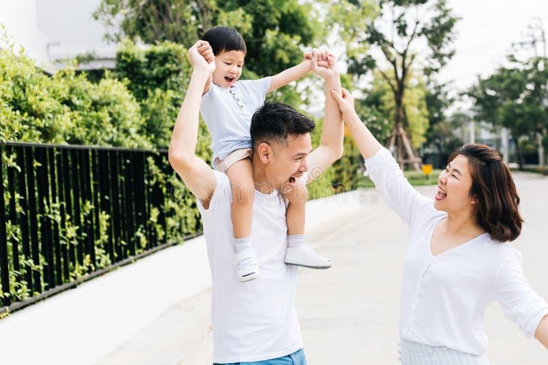 扛在肩上他的儿子的逗人喜爱的亚裔父亲与他的妻子一起在公园 举手的激动的家庭与幸福一起 库存图片