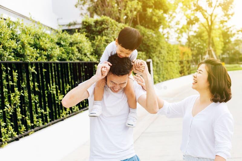 扛在肩上他的儿子的逗人喜爱的亚裔父亲与他的妻子一起在公园 花费时间的激动的家庭与幸福一起 免版税库存图片