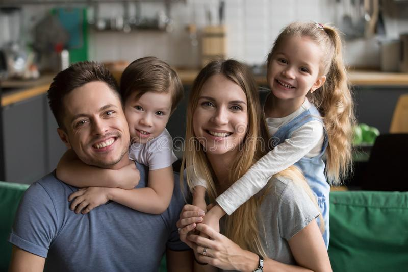 扛在肩上儿子和女儿的愉快的父母坐沙发, por 图库摄影