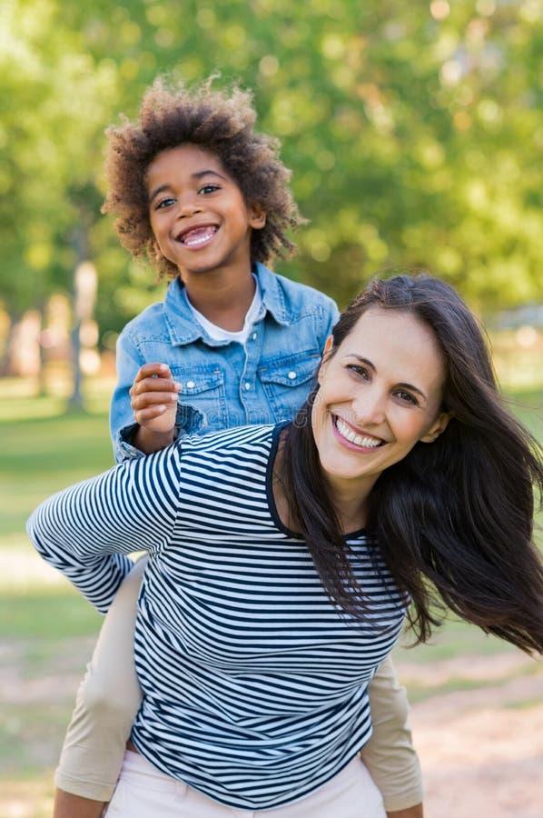 扛在肩上儿子的母亲在公园 图库摄影