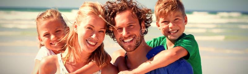 扛在肩上在海滩的愉快的家庭画象 免版税图库摄影
