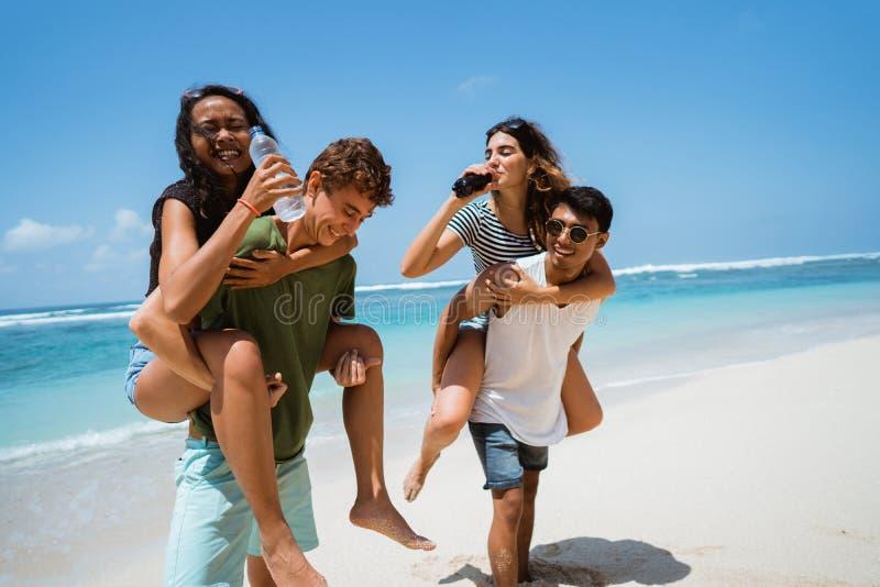 扛在肩上妇女的人拿着软性饮料的瓶 库存照片
