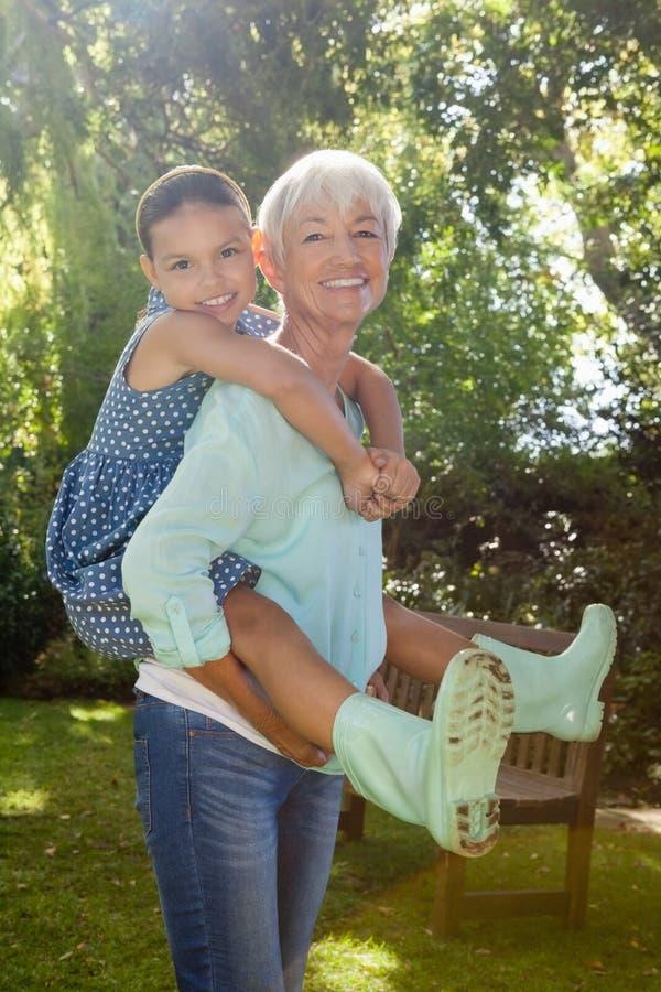 扛在肩上孙女的祖母画象 免版税图库摄影