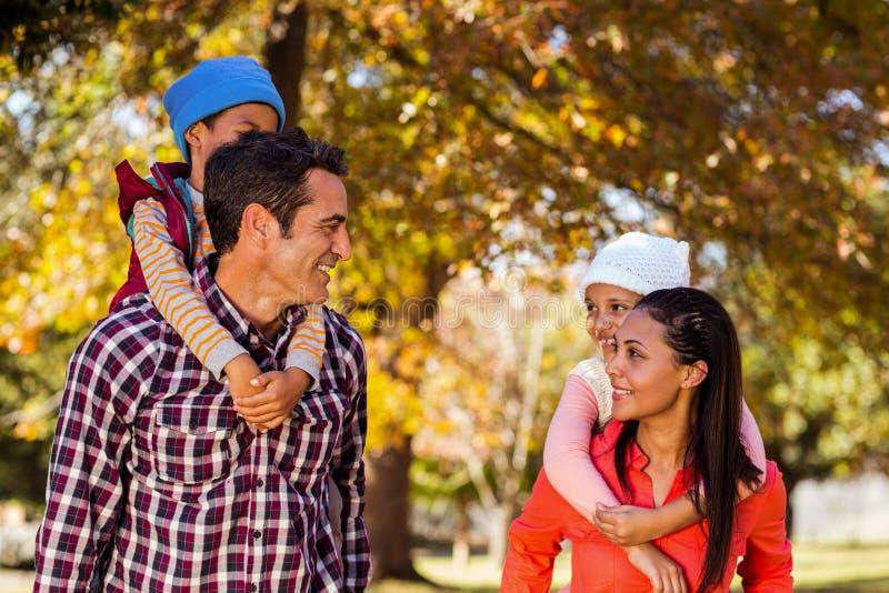 扛在肩上孩子的愉快的父母在公园 免版税库存图片