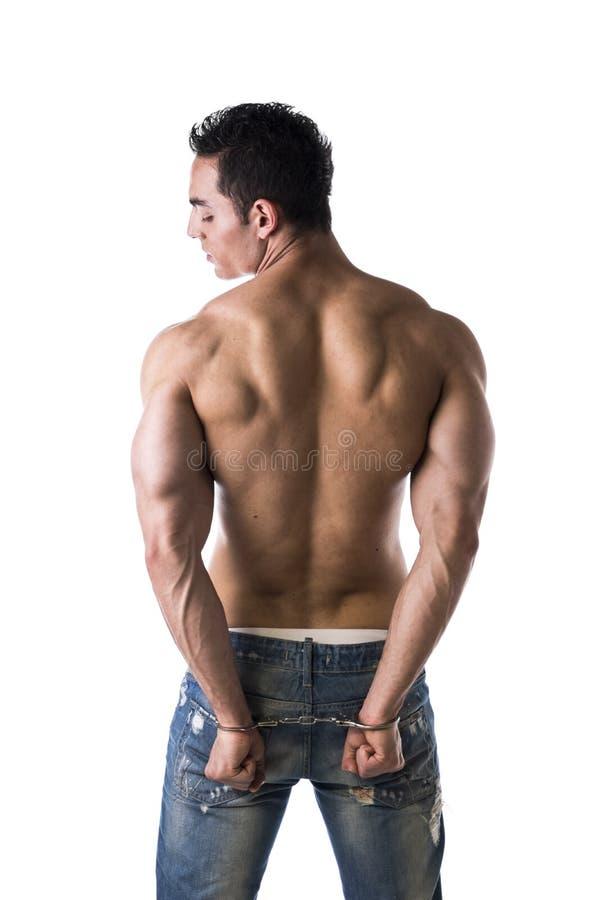 扣上手铐的男性爱好健美者肌肉后面 免版税库存图片