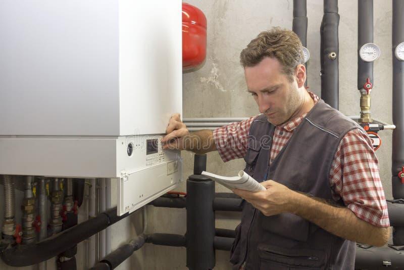 执行一个凝聚的锅炉的维护的水管工 免版税库存照片