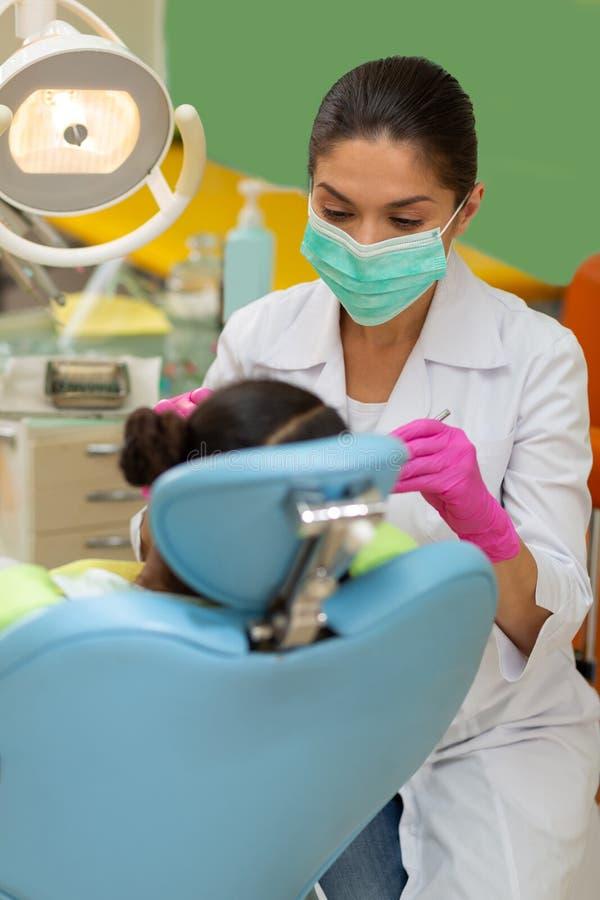 执行一个牙齿检查的严肃的被集中的女性牙医 免版税库存照片