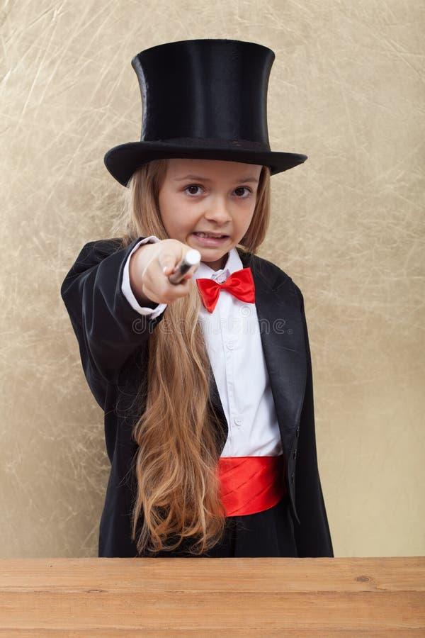 执行一个邪恶的魔术技巧的魔术师女孩-指向与鞭子观察者 免版税库存照片