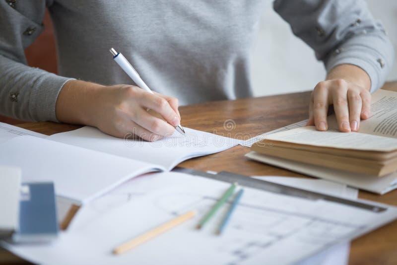 执行一项书面任务的学生女性手在习字簿 库存照片