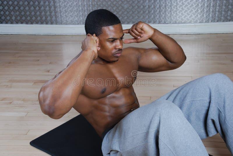 执行仰卧起坐的非洲裔美国人的咬嚼 免版税库存照片