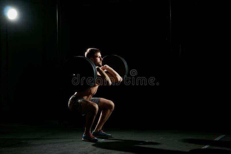 执行健身他的人反映培训水 做与重量的人仰卧起坐 库存图片