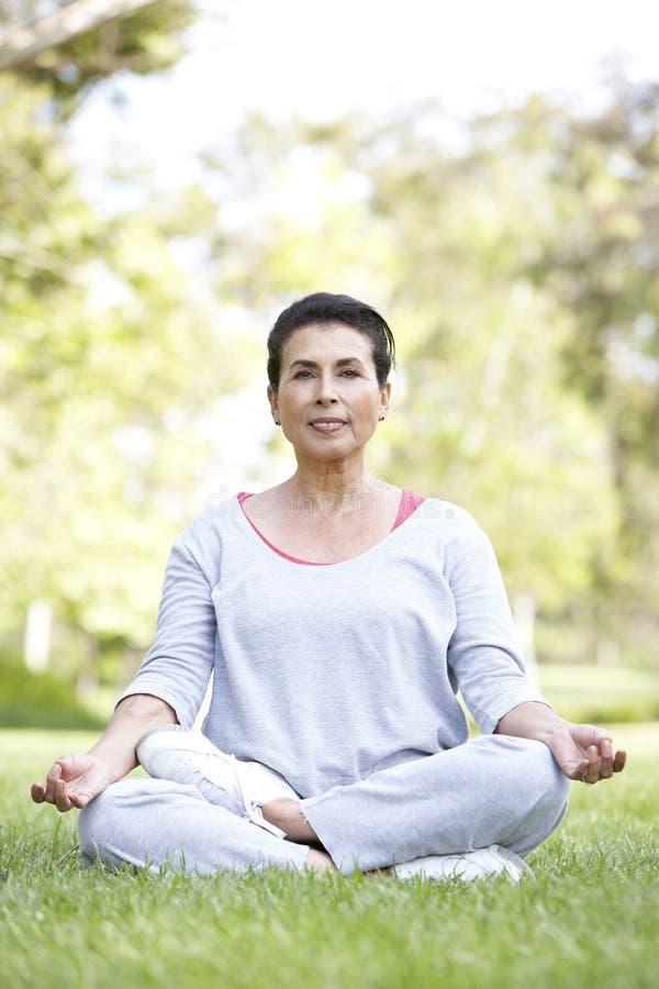 执行公园高级女子瑜伽 免版税库存照片