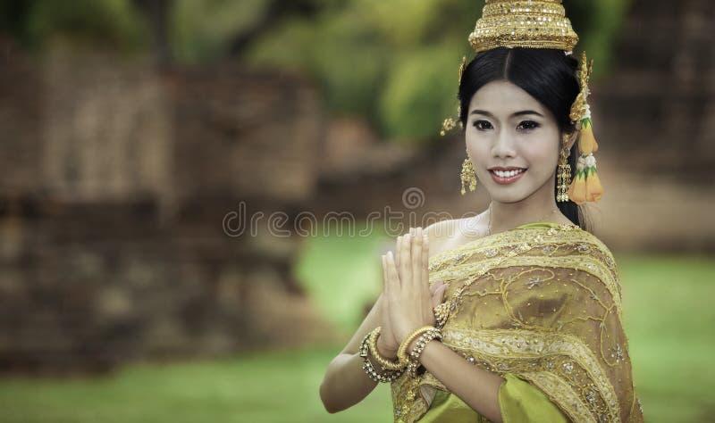 执行典型的泰国舞蹈的妇女与泰国样式寺庙backg 免版税库存图片