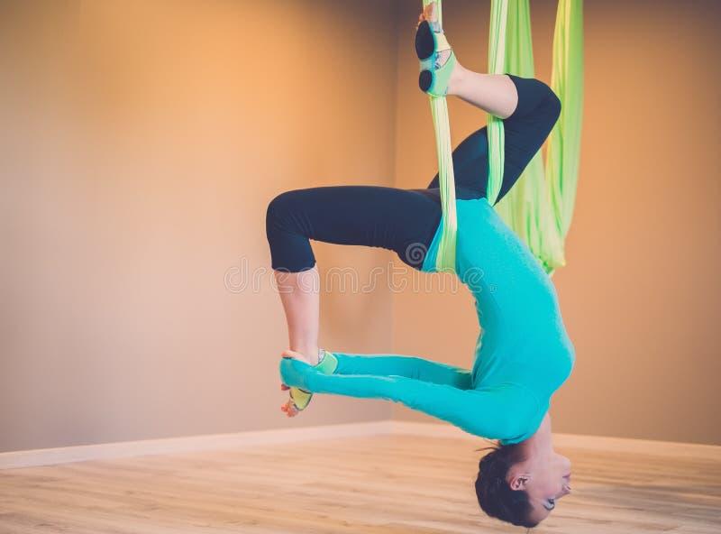 执行反地心引力的瑜伽的妇女 免版税库存图片