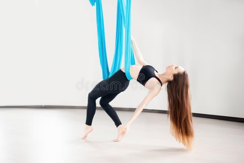 执行反地心引力的空中瑜伽锻炼的年轻女人在白色演播室 概念凝思 免版税库存图片