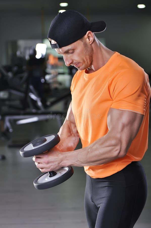 执行哑铃锻炼的英俊的强有力的运动人 免版税图库摄影