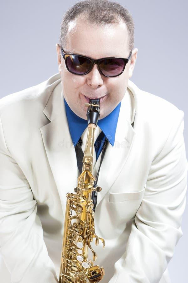 执行在女低音Saxo的幽默男性萨克管演奏员在白色衣服和太阳镜 库存图片