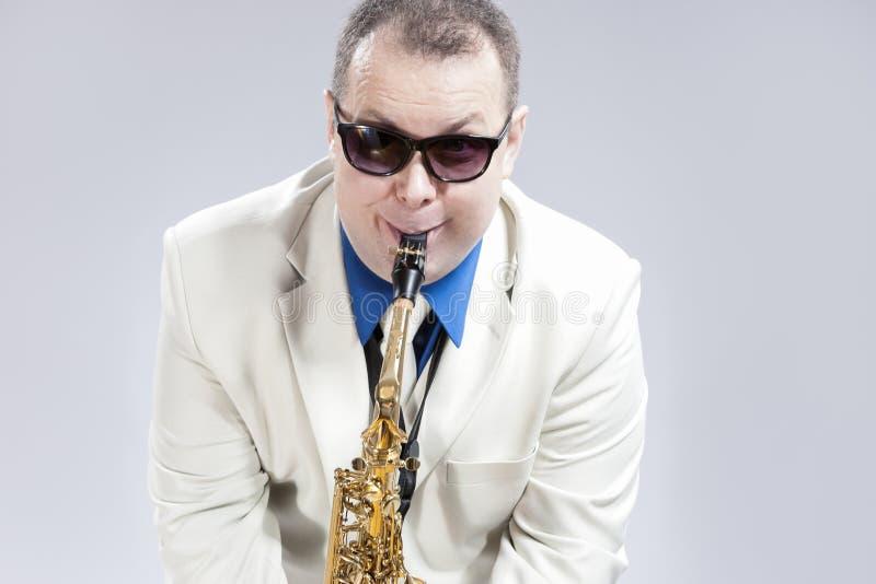 执行在女低音Saxo的滑稽的幽默男性萨克管演奏员 免版税图库摄影