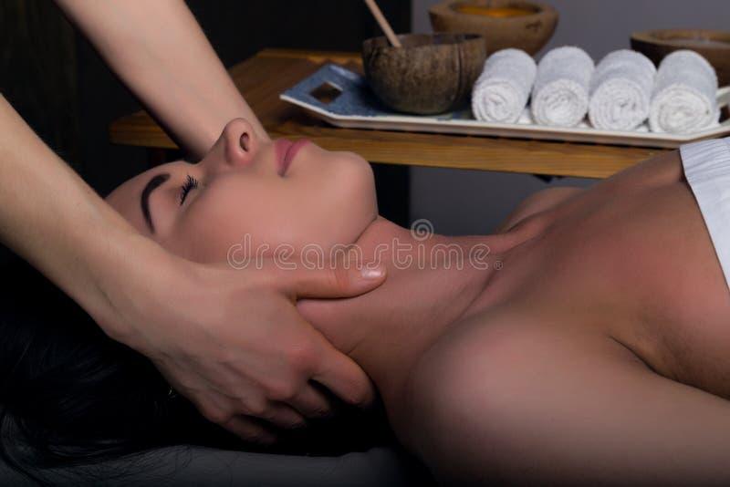 执行在妇女身体的男按摩师按摩温泉沙龙的 轻松的妇女 秀丽处理概念 免版税库存照片
