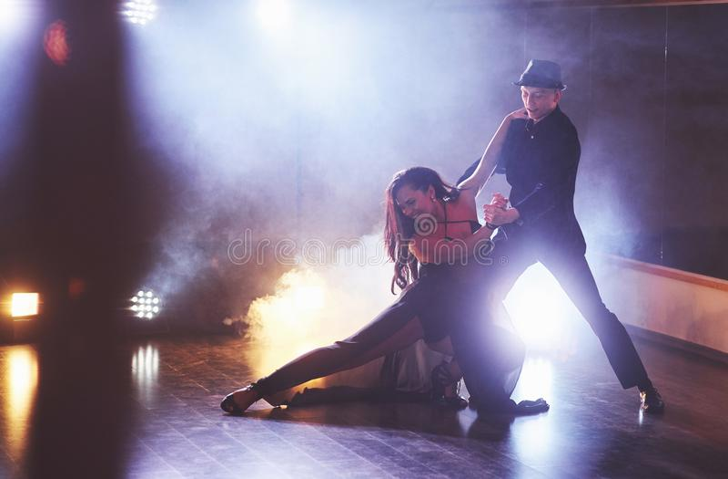 执行在暗室的纯熟舞蹈家在音乐会光和烟下 执行艺术性的肉欲的夫妇 免版税库存照片