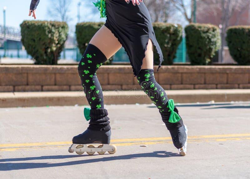 执行在直排轮式溜冰鞋的女孩爱尔兰舞蹈在圣帕特里克的天游行 免版税库存图片