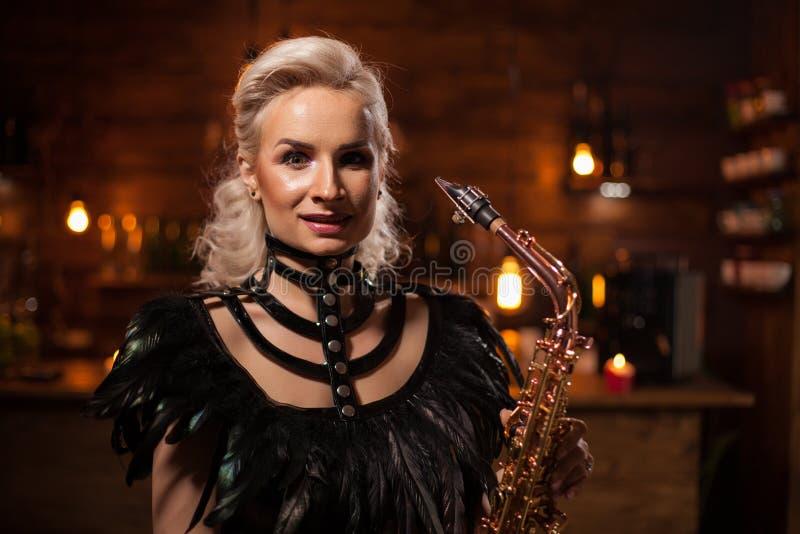 执行在萨克斯管的Atractive年轻女人爵士乐在客栈 免版税库存照片