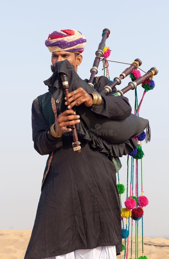 执行在骆驼节日期间的印度吹风笛者在塔尔沙漠,拉贾斯坦,印度 免版税图库摄影